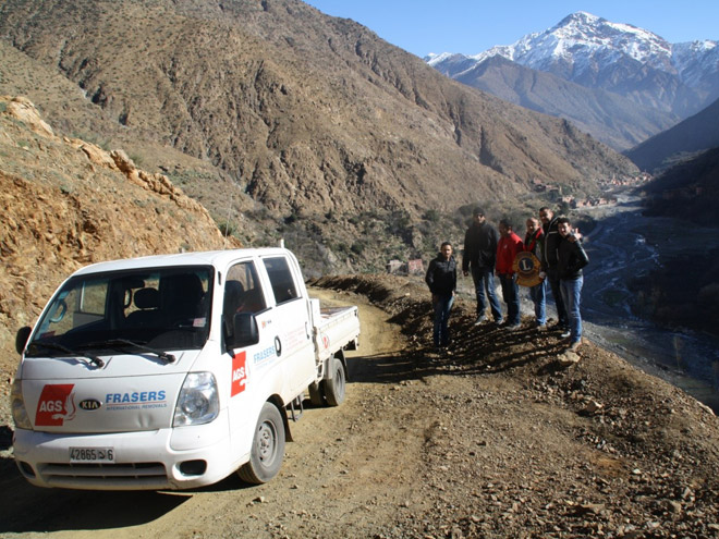 Ags minivan with people posing with mountains at the back