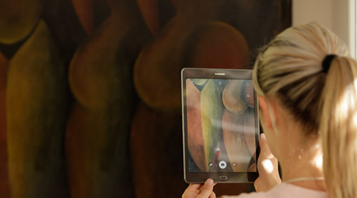 Woman taking a picture of a painting with a tablet.