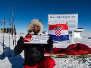 Man holding en AGS banner in Alaska with a Croatian flag at the back