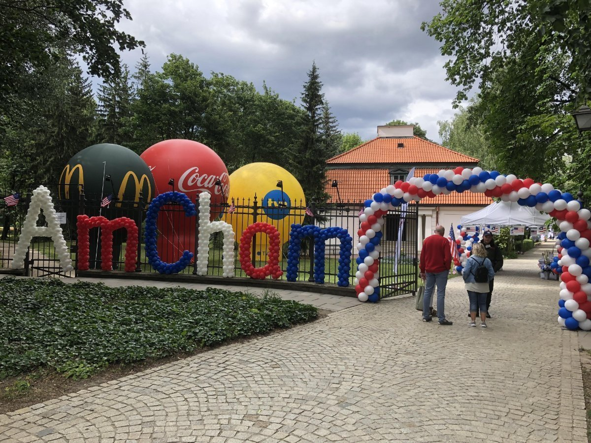 Red, blue and white AmCham logo and balloon arch at the Independance Day Picnic in Poland.